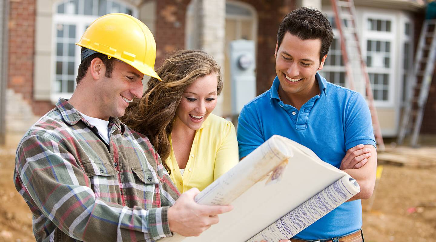 Home builder showing house plans to happy looking couple