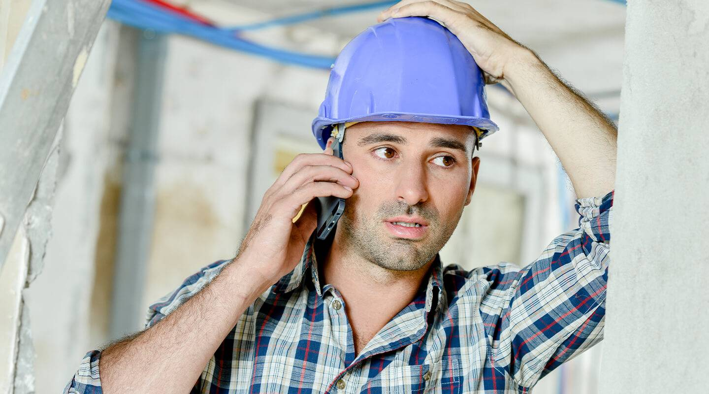 Builder with stressed out look talking over the phone